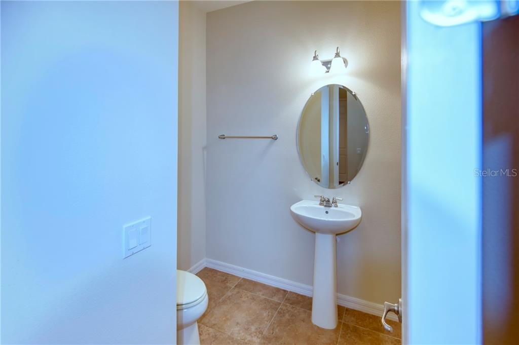 From the laundry room, and great room, there is a handy half bath with pedestal sink.